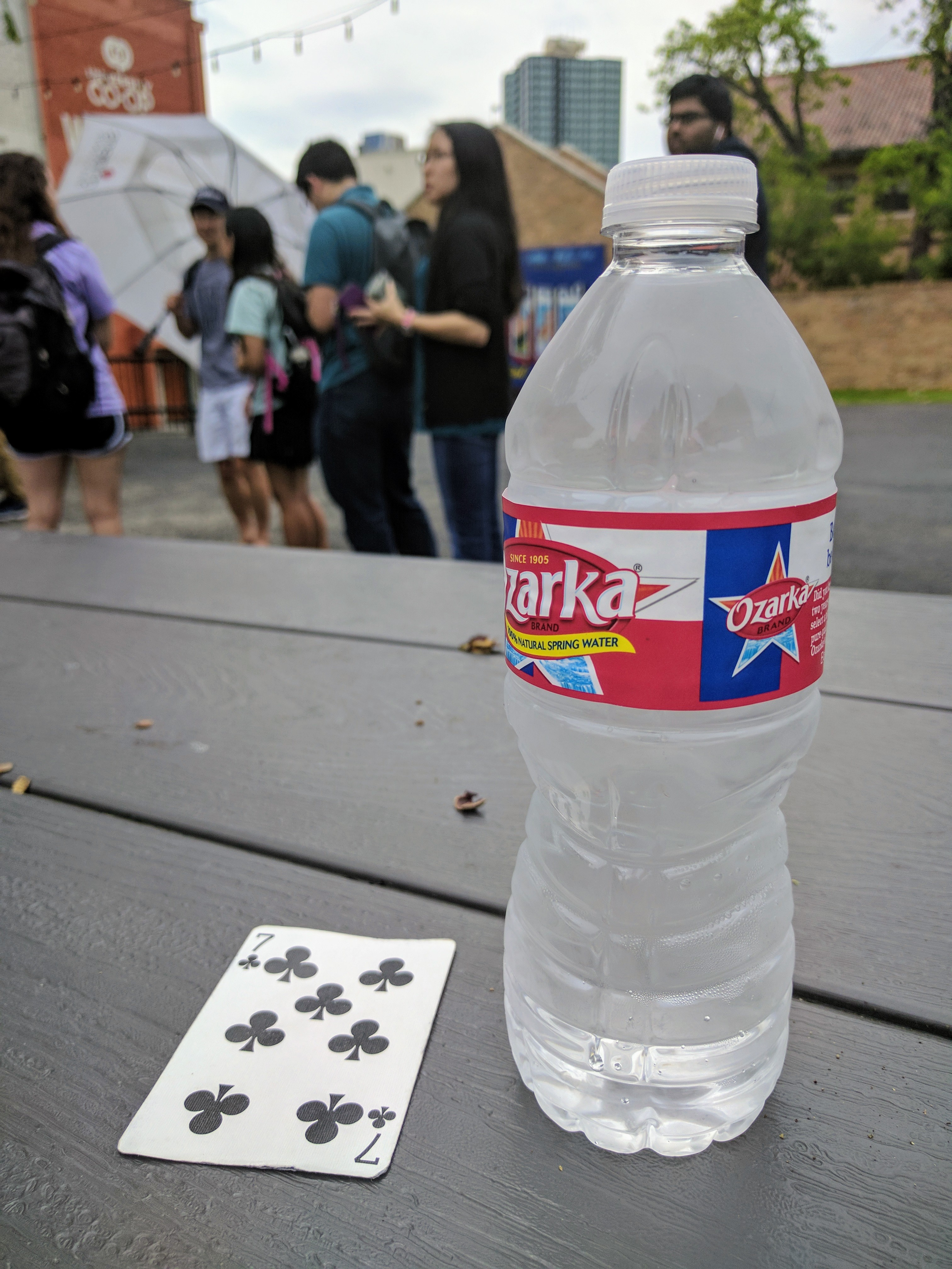 Photo of a playing card next to a bottle of water on a picnic table
