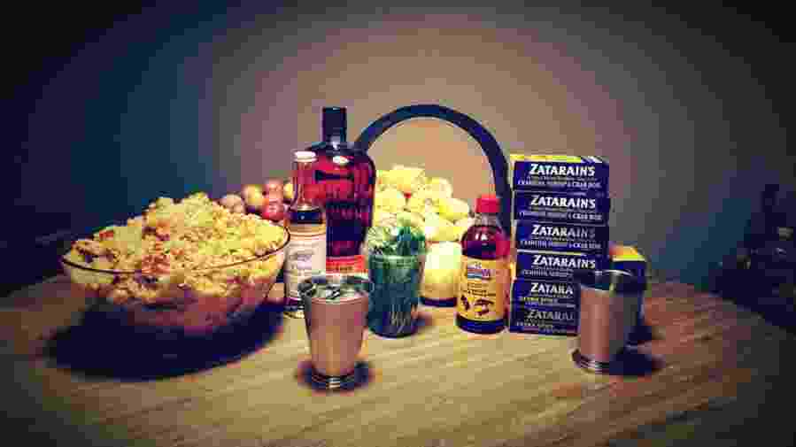 Table spread with jambalaya, whiskey, and crawfish boil supplies