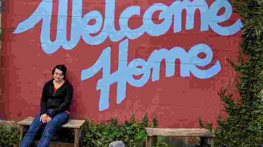 """Girl sitting in front of a sign that says """"Welcome Home"""""""