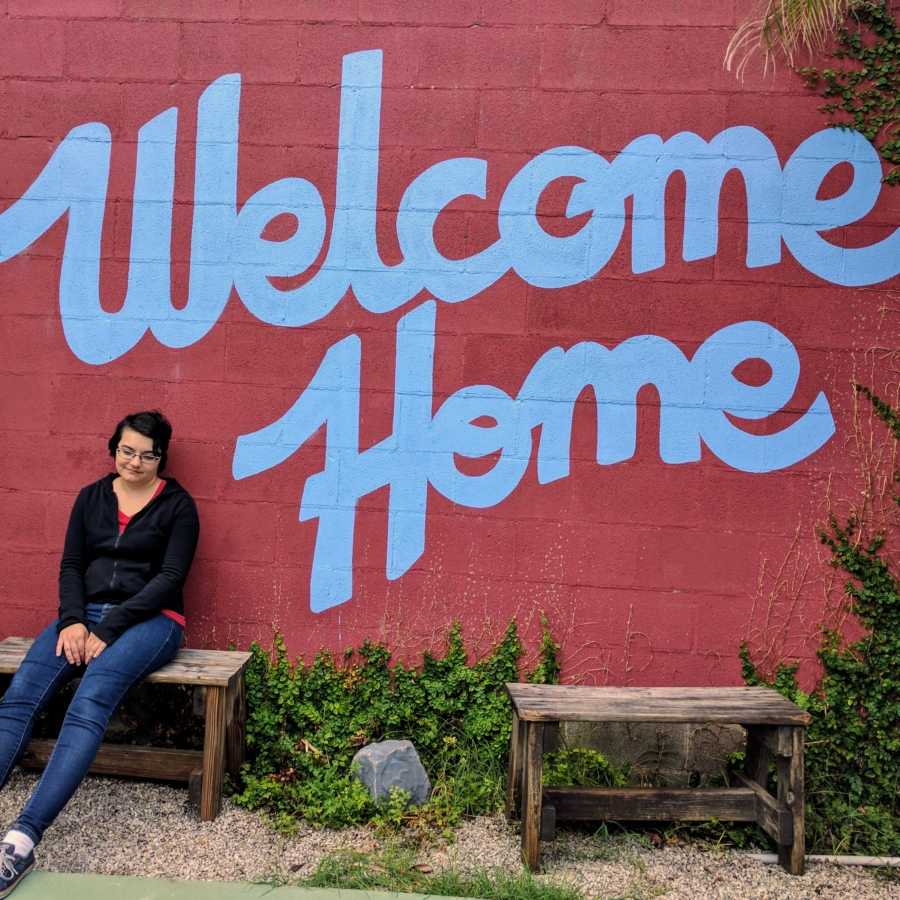 "Girl sitting in front of a sign that says ""Welcome Home"""