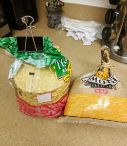 A bag of tostadas with a binder clip and a bag of brown sugar with a rubberband.